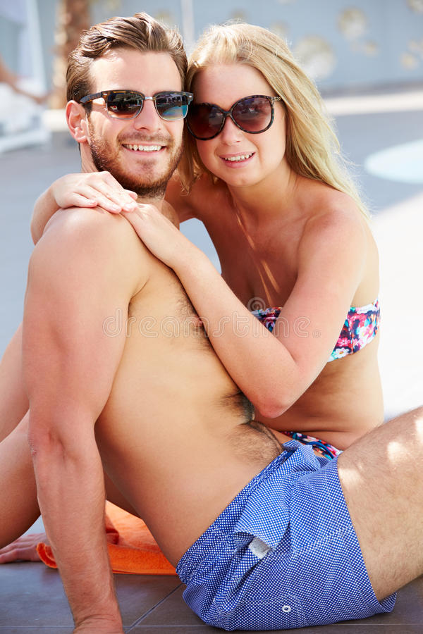 Jeunes couples en vacances détendant par la piscine photographie stock