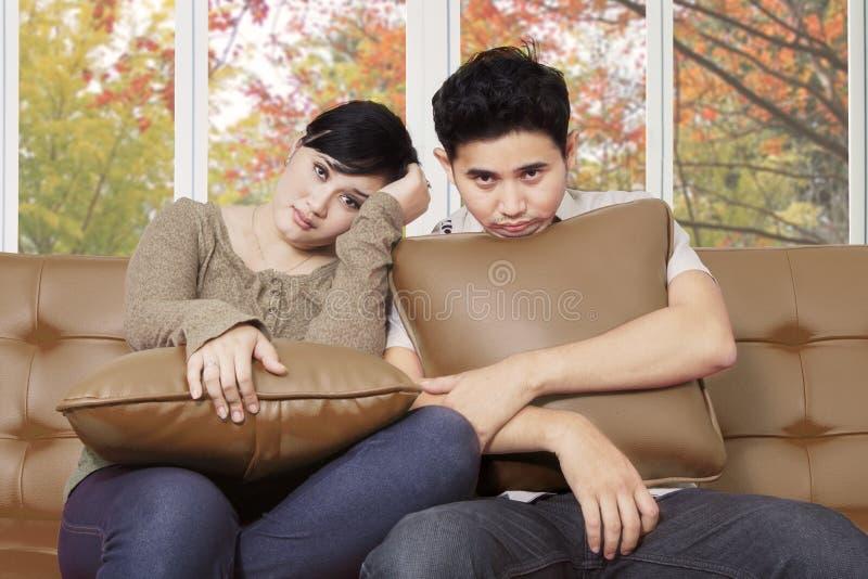 Jeunes couples ennuyés à la maison image stock