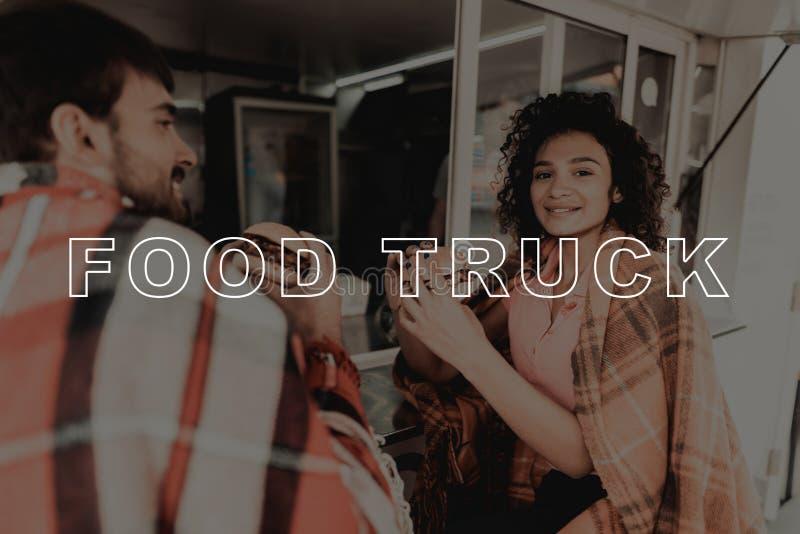 Jeunes couples enveloppés dans des plaids Consommation de camion de nourriture photo stock