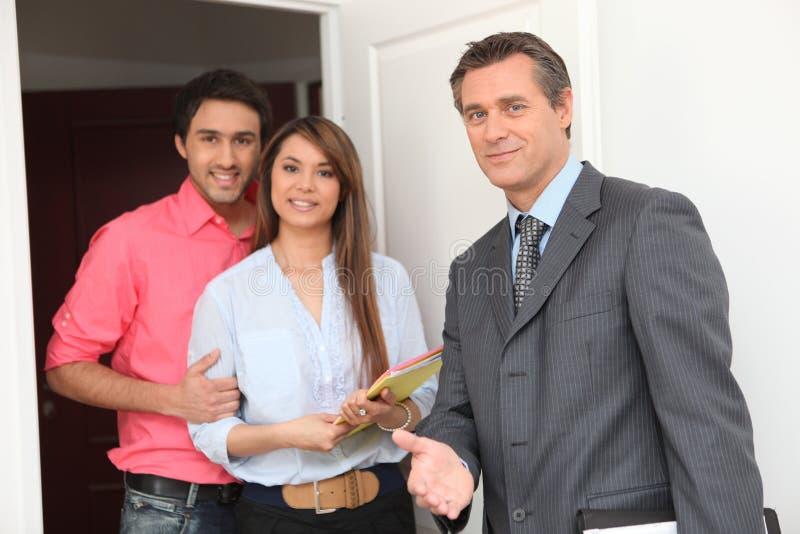 Jeunes couples et agent immobilier photo stock