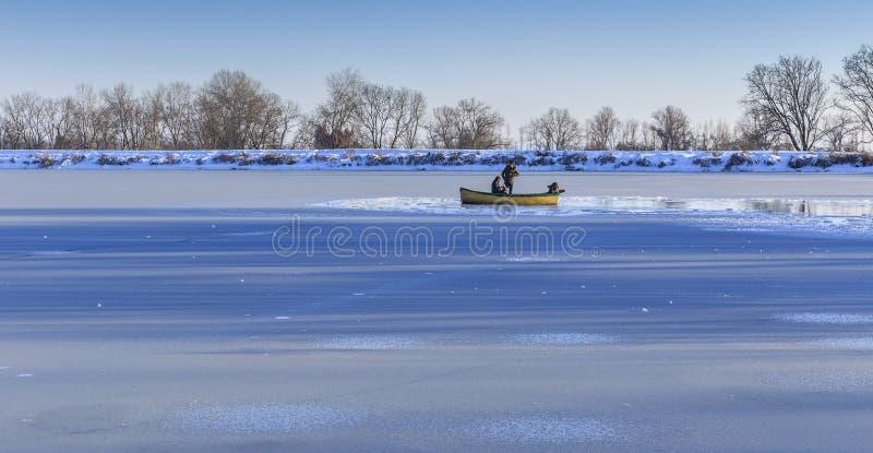 Jeunes couples et photographe dans un bateau sur un lac congelé images stock