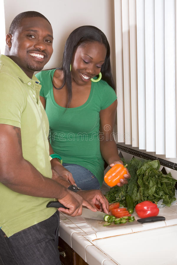 Jeunes couples ethniques sur la cuisine découpant des légumes en tranches image stock