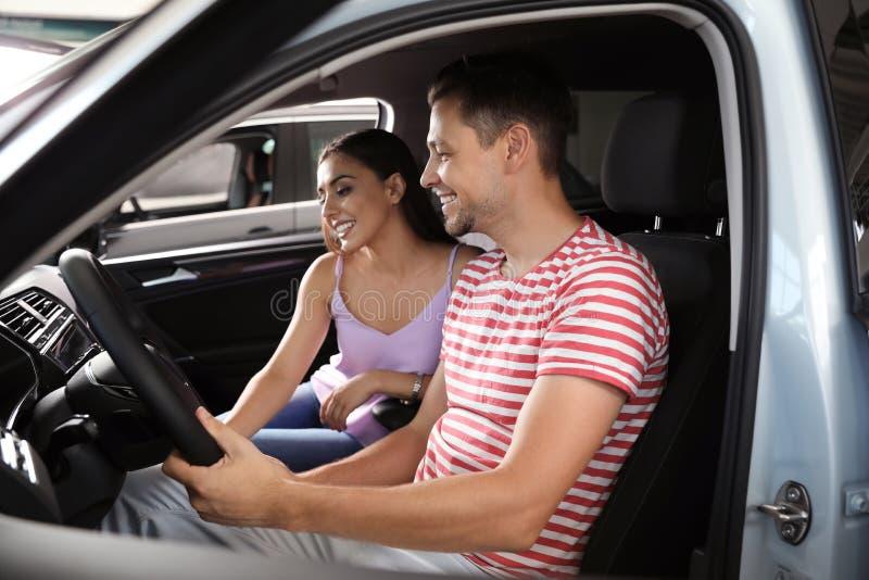 Jeunes couples examinant la nouvelle voiture photos stock