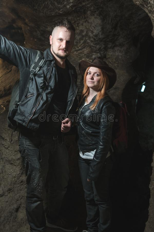 Jeunes couples explorant la caverne énorme Les voyageurs d'aventure ont habillé le chapeau de cowboy et le sac à dos, veste en cu photo stock