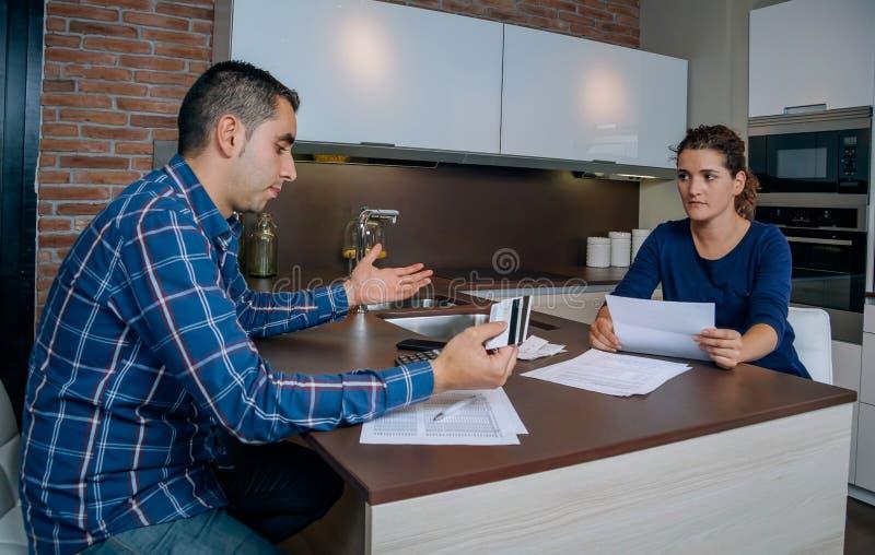 Jeunes couples fâchés discutant par des dettes de carte de crédit photographie stock