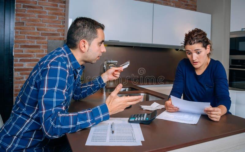 Jeunes couples fâchés discutant par des dettes de carte de crédit photos libres de droits