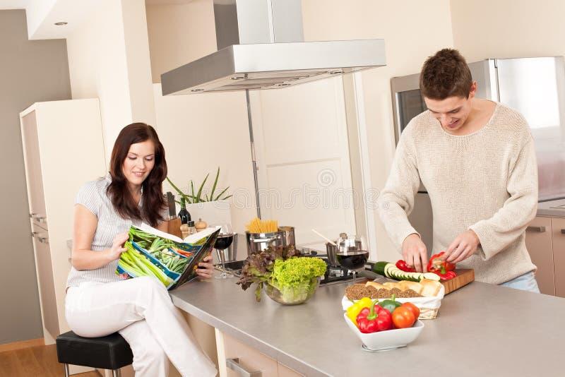 Jeunes couples faisant cuire dans la cuisine ensemble photographie stock libre de droits