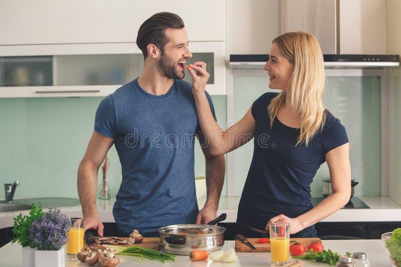 Jeunes couples faisant cuire ensemble la préparation de repas d'intérieur photographie stock