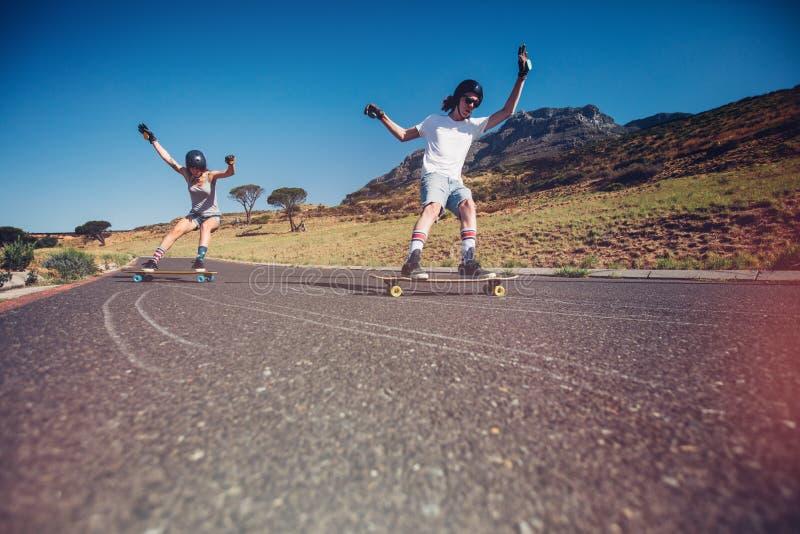 Jeunes couples faisant de la planche à roulettes sur la route photos stock