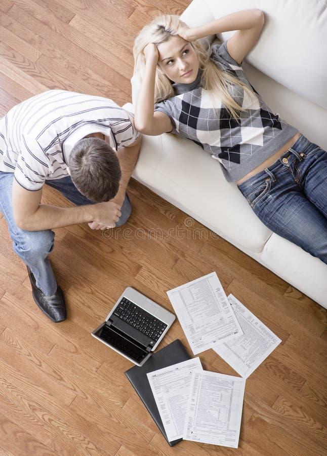 Jeunes couples faisant des impôts images stock