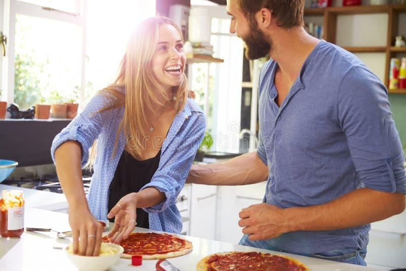 Jeunes couples faisant la pizza dans la cuisine ensemble photos stock