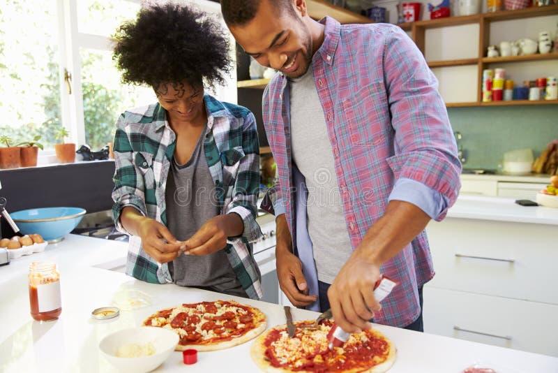Jeunes couples faisant la pizza dans la cuisine ensemble photo libre de droits