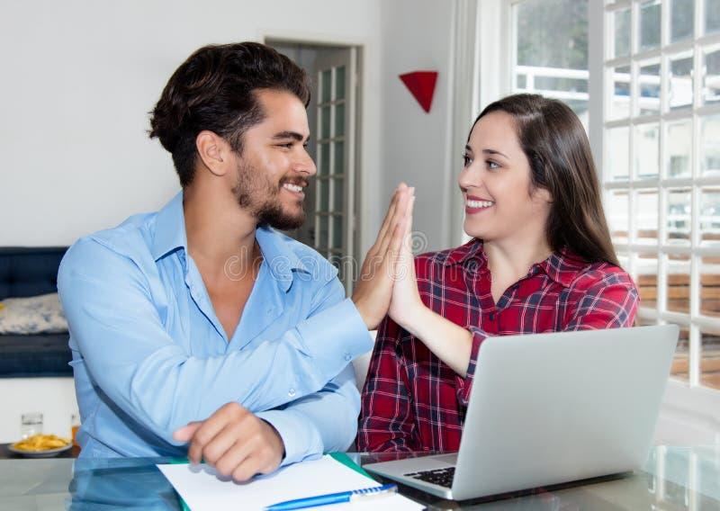 Jeunes couples faisant la réservation en ligne avec l'ordinateur portable image libre de droits