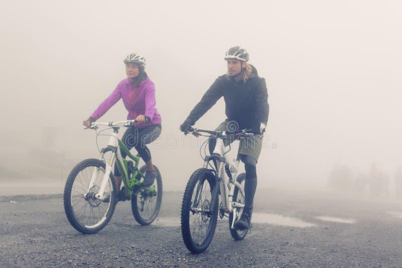 Jeunes couples faisant un cycle par le brouillard images stock