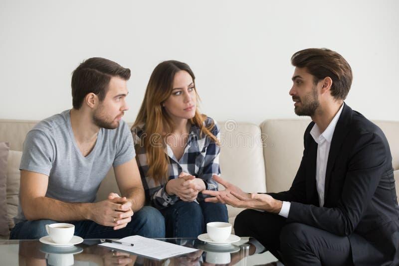 Jeunes couples, famille à rencontrer l'agent immobilier, dessinateur d'intérieurs photos libres de droits