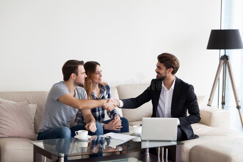 Jeunes couples, famille faisant l'affaire avec l'agent immobilier, dessinateur d'intérieurs photographie stock