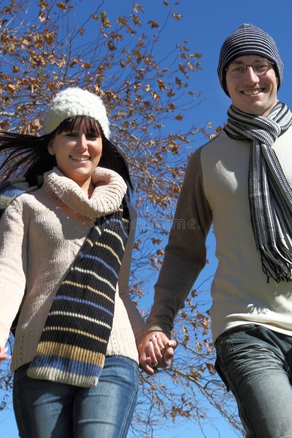 Jeunes couples fonctionnant dans des vêtements de l'hiver images stock