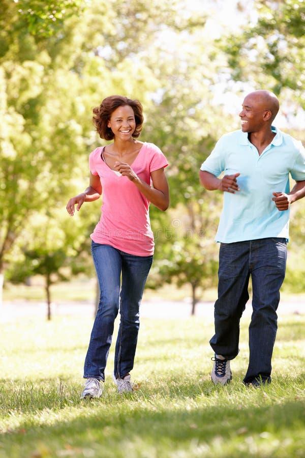 Jeunes couples fonctionnant en stationnement image libre de droits