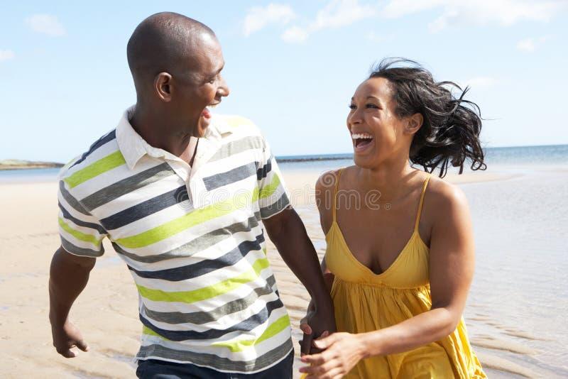 Jeunes couples fonctionnant le long de la fixation H de rivage photo libre de droits