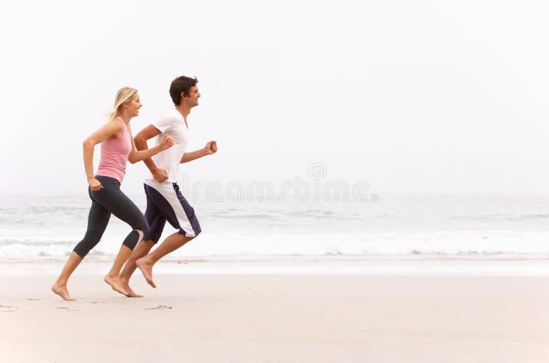 Jeunes couples fonctionnant le long de la plage de l'hiver image libre de droits
