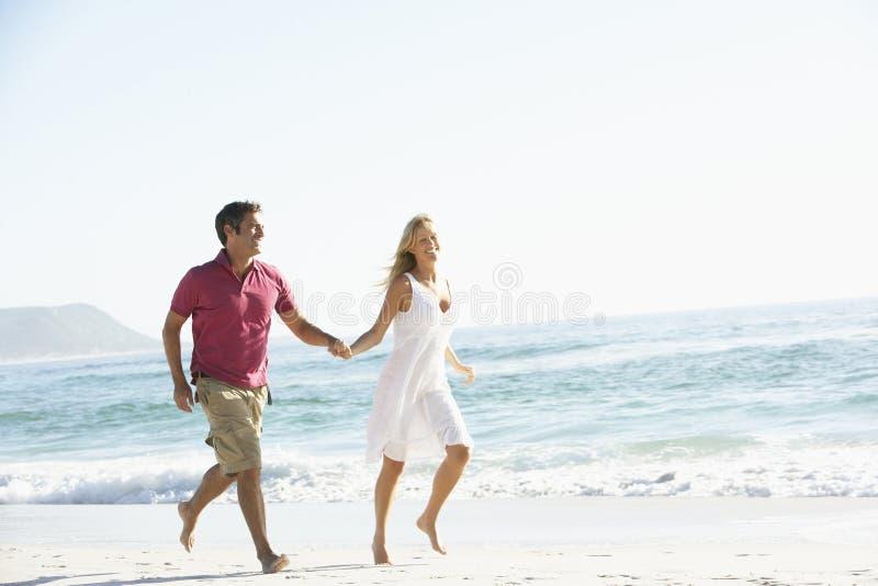 Jeunes couples fonctionnant le long de Sandy Beach en vacances photo stock