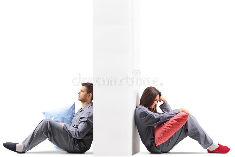 Jeunes couples fous à l'un l'autre s'asseyant des bords opposés d'un wa image stock