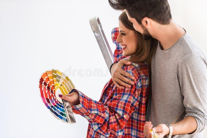 Jeunes couples gais choisissant la couleur pour la maison de peinture images stock