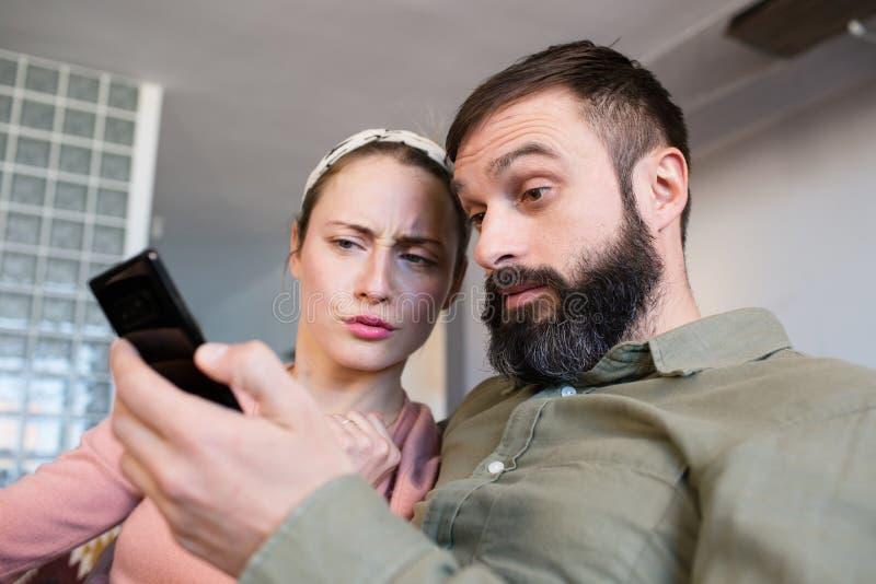 Jeunes couples gais utilisant le smartphone à l'endroit de moder Relations romantiques entre les personnes images libres de droits