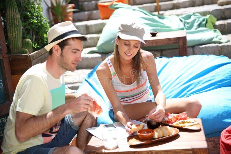 Jeunes couples goûtant la nourriture locale photographie stock