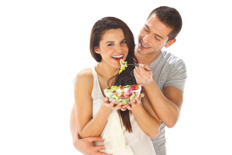 Couples heureux mangeant de la salade ensemble sur un fond blanc image stock