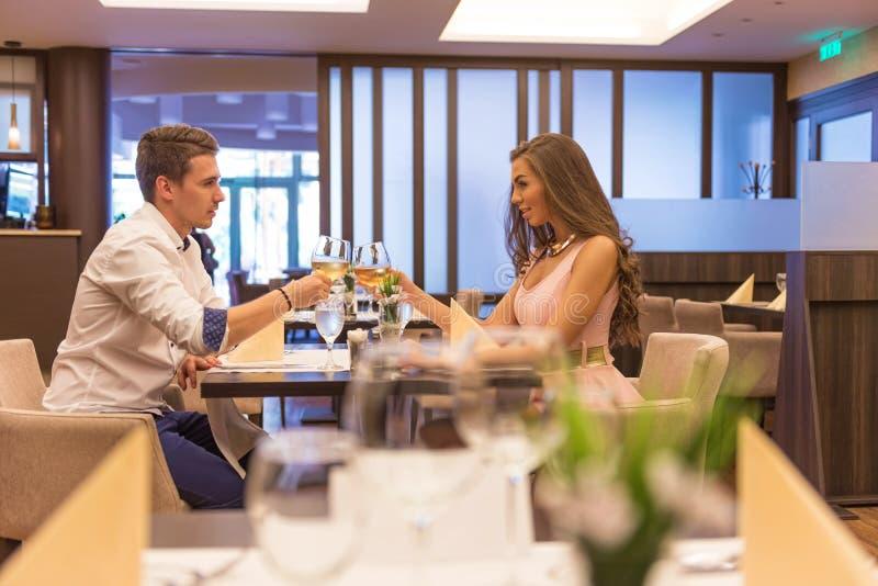 Jeunes couples grillant dans le restaurant avec des verres de vin images stock