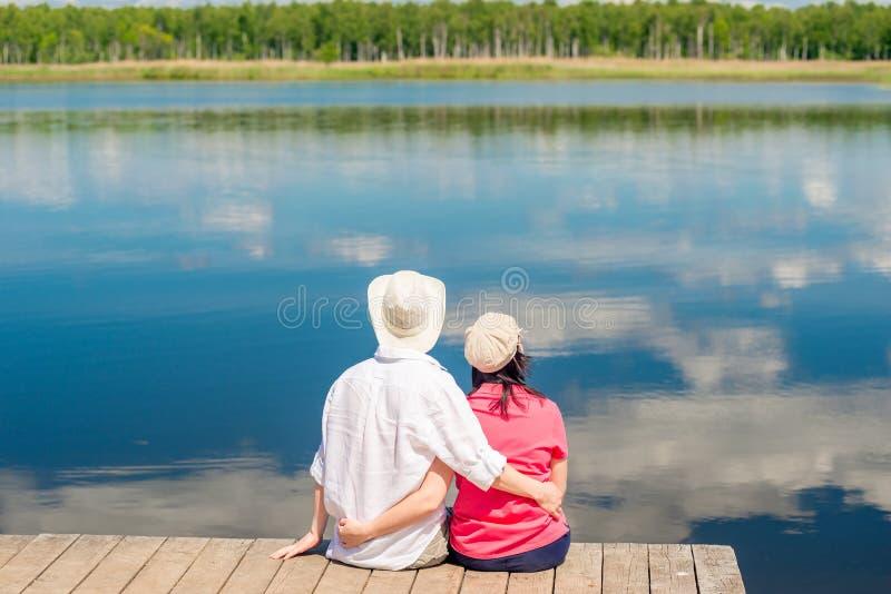 Jeunes couples heureux étreignant et appréciant le repos près du beau lac photographie stock libre de droits