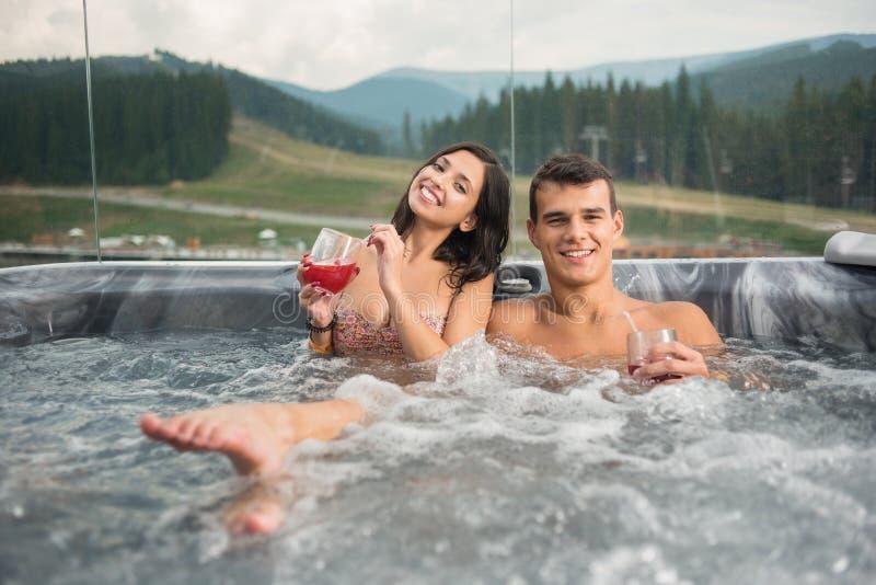 Jeunes couples heureux appréciant un bain dans le jacuzzi tout en buvant le cocktail dehors des vacances romantiques photo stock