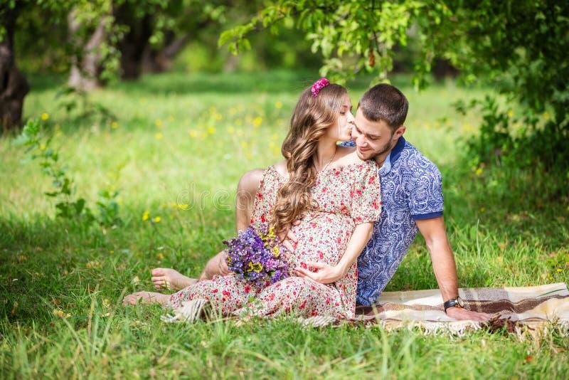 Jeunes couples heureux attendant le bébé, femme enceinte embrassant son mari image libre de droits
