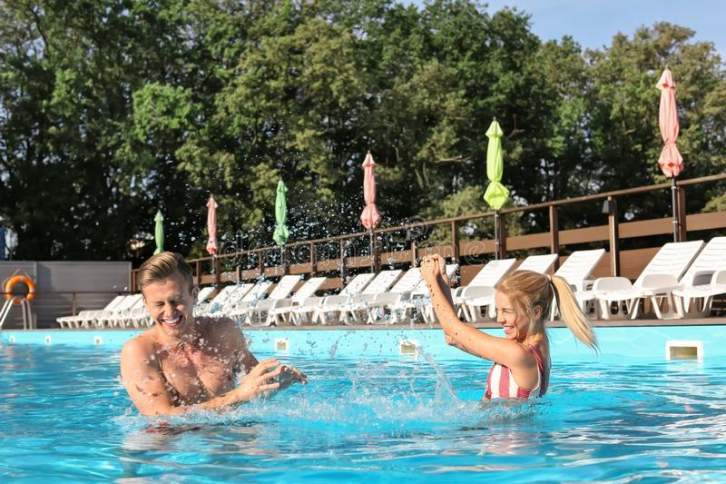 Jeunes couples heureux ayant l'amusement dans la piscine à la station de vacances photographie stock