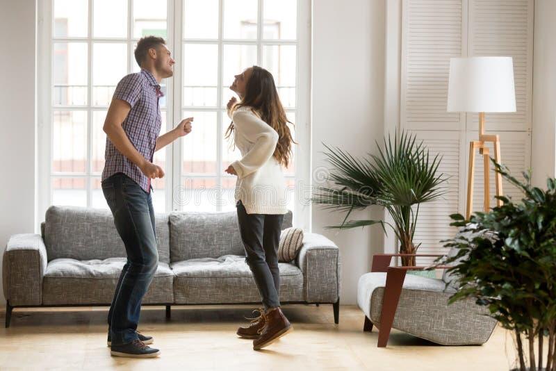 Jeunes couples heureux ayant l'amusement dansant ensemble dans le salon photographie stock libre de droits