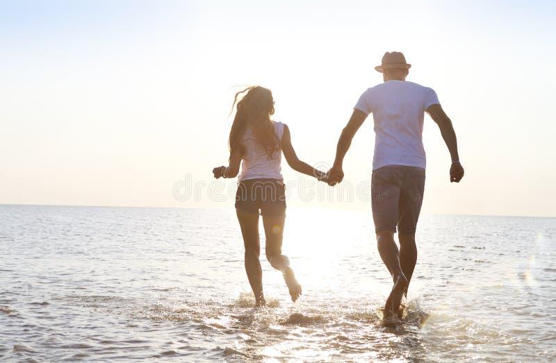 Jeunes couples heureux ayant l'amusement fonctionnant sur la plage au coucher du soleil images libres de droits