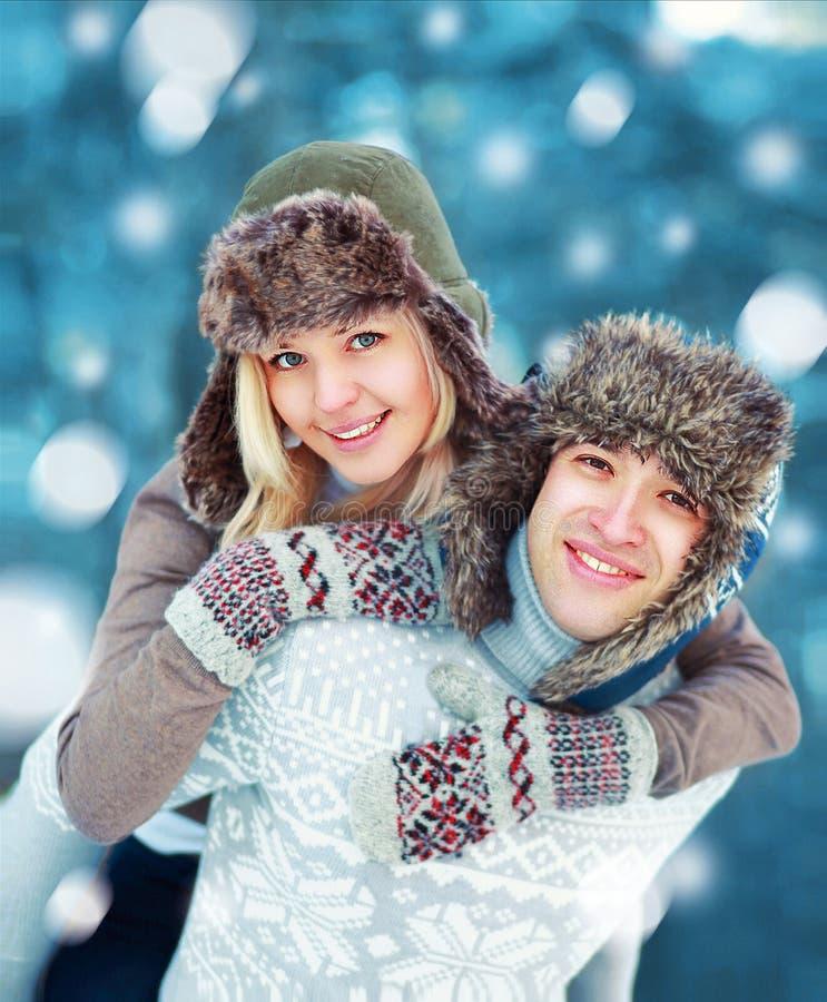 Jeunes couples heureux ayant l'amusement jouant dehors en hiver photographie stock libre de droits