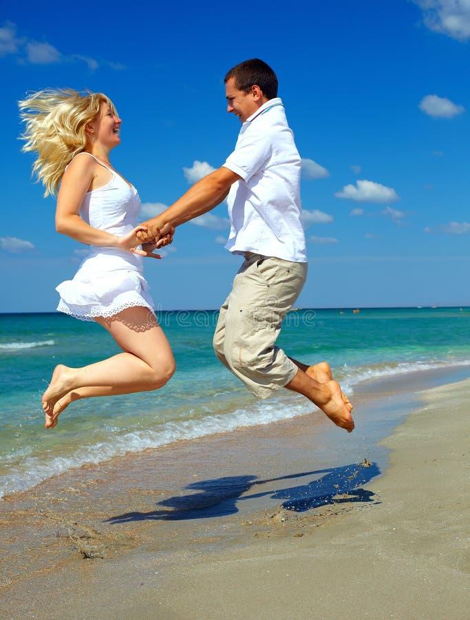 Jeunes couples heureux ayant l'amusement sur la plage de mer image libre de droits