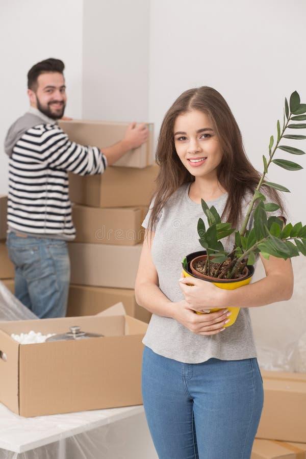 Jeunes couples heureux déballant des boîtes et entrant dans une nouvelle maison images stock