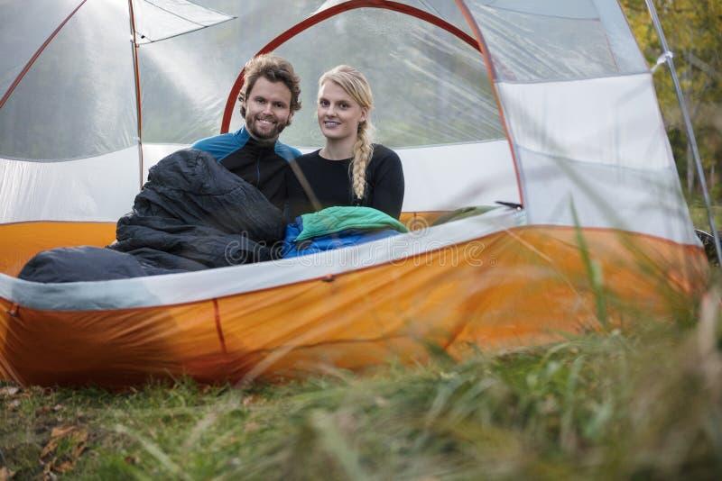 Jeunes couples heureux détendant dans la tente à la forêt images libres de droits