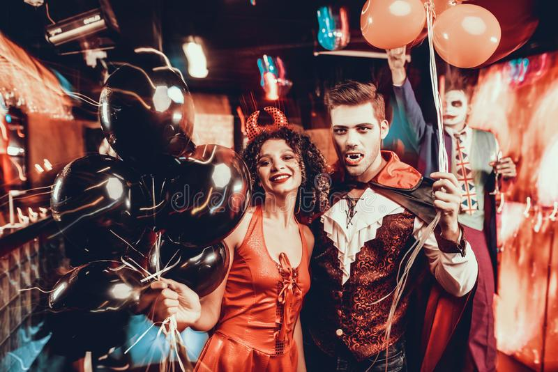 Jeunes couples heureux dans des costumes à la partie de Halloween photo libre de droits