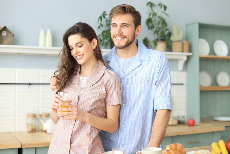 Jeunes couples heureux dans des pyjamas dans la cuisine à la maison regardant à partir de la caméra, matin image stock