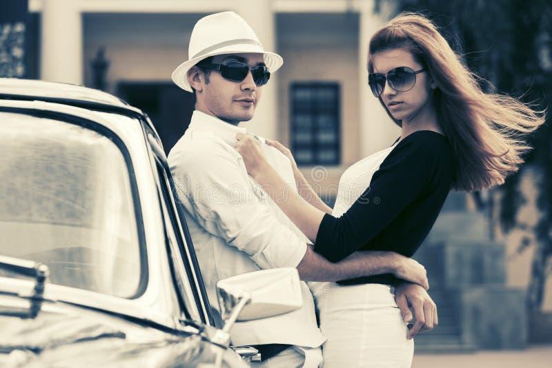Jeunes couples heureux dans l'amour en dehors d'une voiture de vintage photographie stock libre de droits