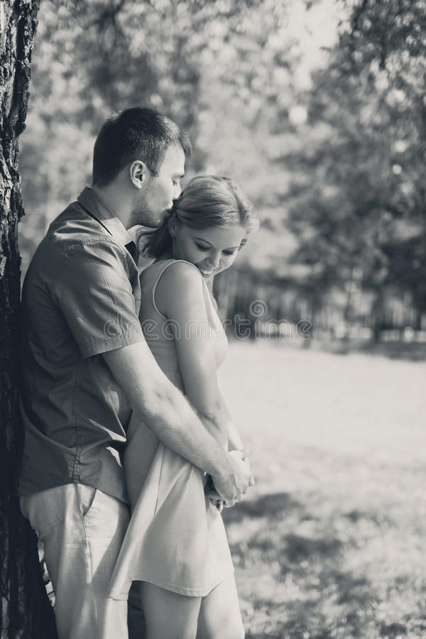 Jeunes couples heureux dans l'amour, homme étreignant la femme, rétro photo blanche noire photos stock