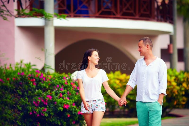 Jeunes couples heureux dans l'amour marchant sur la rue des vacances photos stock