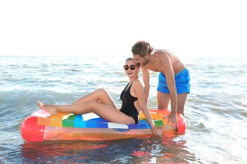 Jeunes couples heureux dans la natation de tenue de plage avec le matelas gonflable image libre de droits