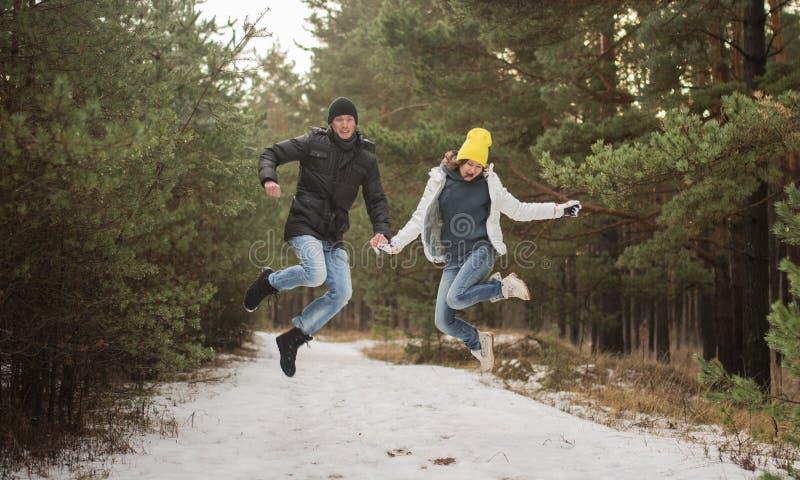 Jeunes couples heureux dans sauter de parc d'hiver Famille à l'extérieur Amour image stock