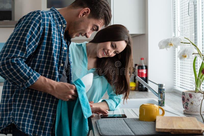 Jeunes couples heureux dans une cuisine avec les plats propres dans les mains de la montre au smartphone La vue du côté photos stock