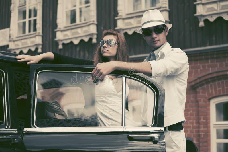 Jeunes couples heureux de mode dans l'amour en dehors d'une voiture de cru photographie stock